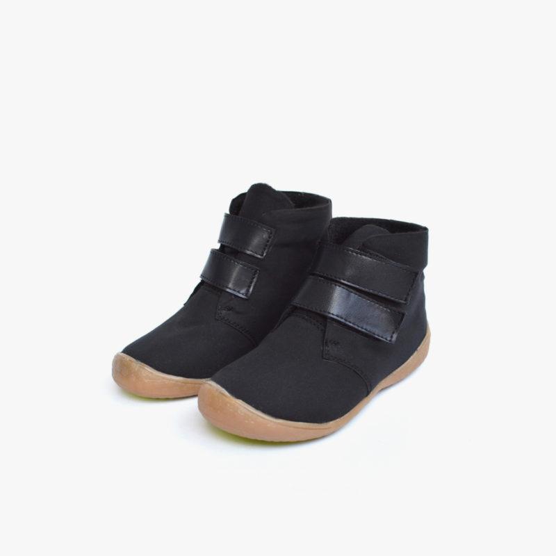 Ansicht von vorn auf ein Paar vegane warme Kinderschuhe aus wasserdichter Bio-Baumwolle in schwarz mit hoher Gummisohle und dunkelblauen Klettverschlüssen von Sorbas Shoes Berlin.